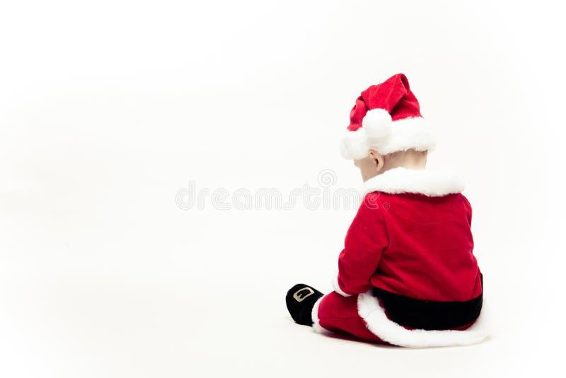 Santa Claus-de baby in rode Kerstmiskleren zit met zijn die rug op wit wordt geïsoleerd stock fotografie