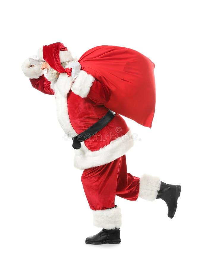 Santa Claus de corrida com saco completamente dos presentes no fundo branco imagens de stock royalty free