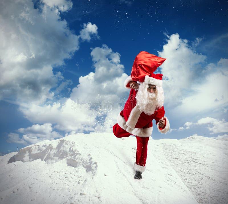 Santa Claus de funcionamiento en nieve fotos de archivo