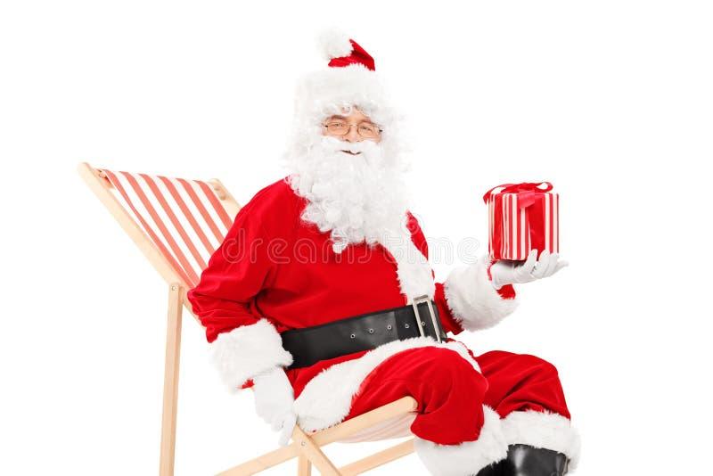 Santa Claus de sourire s'asseyant sur une chaise et tenir de plage un cadeau photos stock