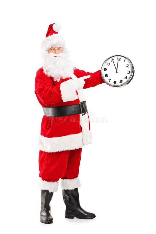 Santa Claus de sourire se dirigeant sur une horloge photo libre de droits