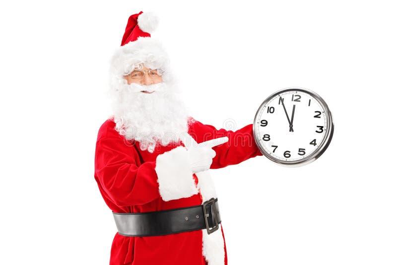 Santa Claus de sourire se dirigeant sur une horloge photo stock