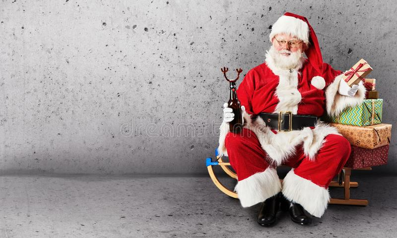 Santa Claus-de zitting op een slee met Kerstmisgiften en stelt op een duidelijke achtergrond met exemplaarruimte voor royalty-vrije stock afbeeldingen