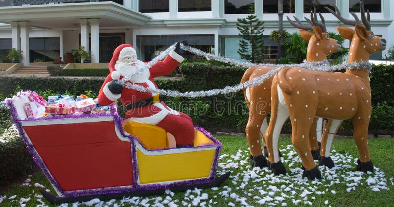 Santa Claus delivers gifts in a sleigh drawn by reindeer, decorative garden sculpture, summer Christmas royalty free stock photos