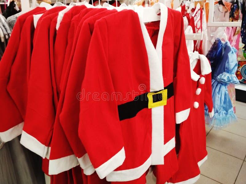 Santa Claus den original- kläderna på kläderstander i shoppar arkivfoto