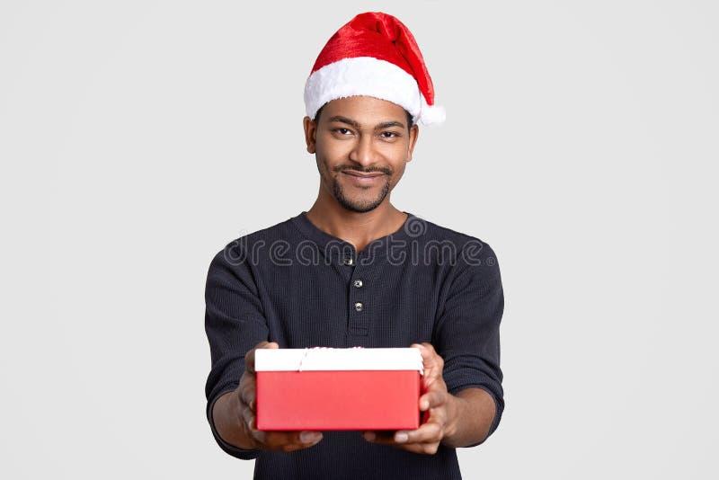 Santa Claus descascada escura veste o chapéu festivo, ligação em ponte ocasional, guarda a caixa atual, sorrisos gladfully, isola fotografia de stock royalty free