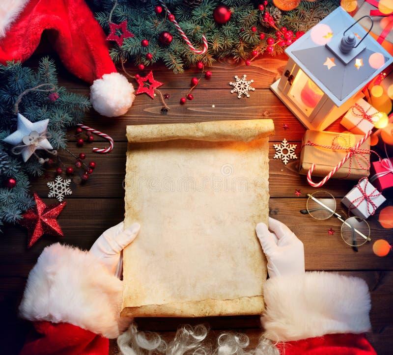 Santa Claus Desk Reading Wish List med prydnaden royaltyfri foto