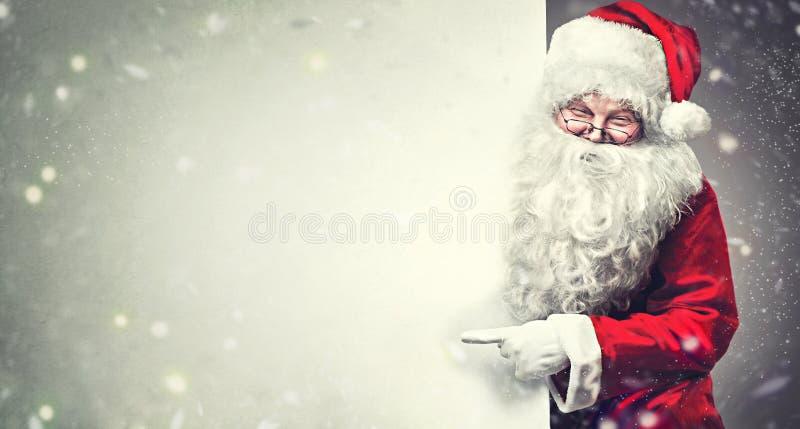 Santa Claus, die auf leeren Anzeigenfahnenhintergrund mit Kopienraum zeigt lizenzfreie stockbilder