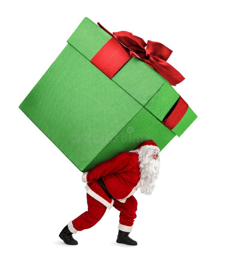 Santa Claus, die das enorme Geschenk lokalisiert auf Weiß trägt lizenzfreie stockfotografie