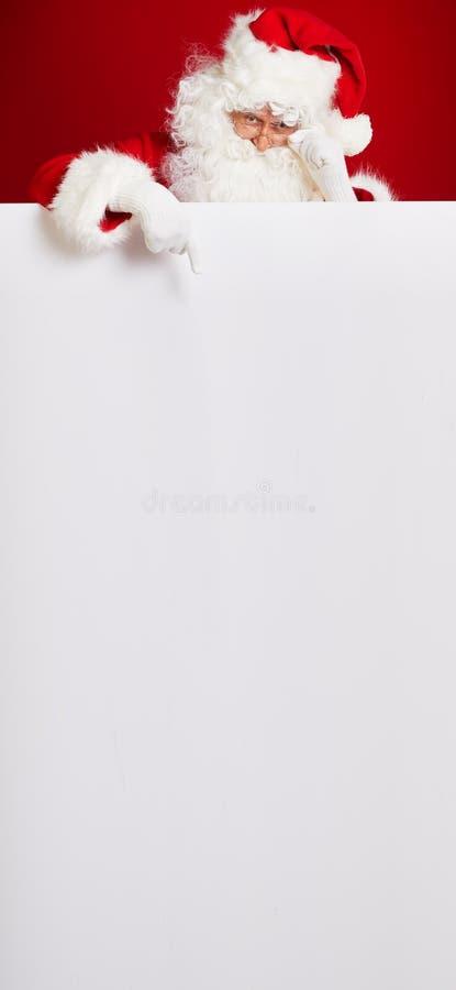 Santa Claus, die in die leere Anzeigenfahne lokalisiert auf r zeigt stockbild