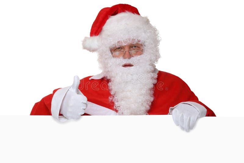Santa Claus die duimen op Kerstmis met lege banner tonen en stock foto