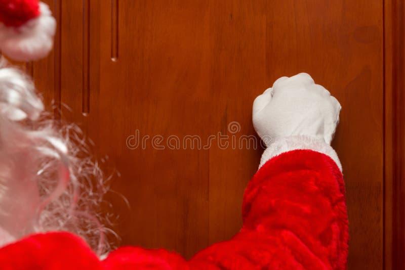 Santa Claus die een deur kloppen stock afbeelding