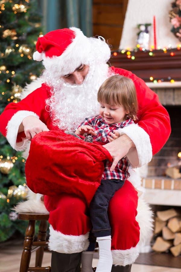 Santa Claus die een heden van zak geven aan jong geitjejongen royalty-vrije stock foto