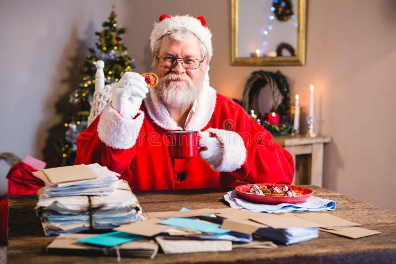 Santa Claus die een koekje met koffie hebben royalty-vrije stock foto's