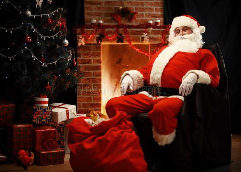 Santa Claus die een rust als comfortabele voorzitter hebben stock foto's