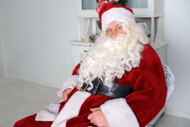 Santa Claus die een rust als comfortabele voorzitter hebben thuis royalty-vrije stock afbeelding