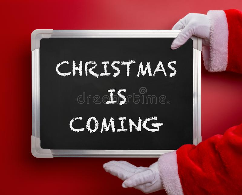 Santa Claus die een zwart die schoolbord houden met KERSTMIS wordt geschreven KOMT op rood royalty-vrije stock afbeelding