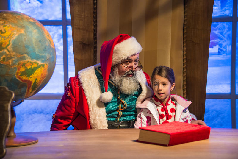 Santa Claus, die ein kleines Mädchen in ihren Armen vor seinem De hält lizenzfreie stockfotografie