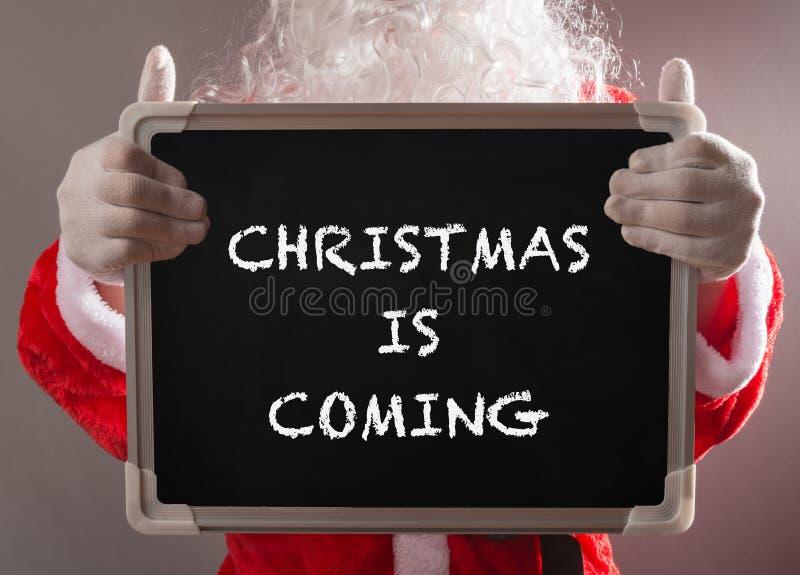 Santa Claus, die ein schwarzes Kreidebrett geschrieben mit WEIHNACHTEN hält, KOMMT stockfoto