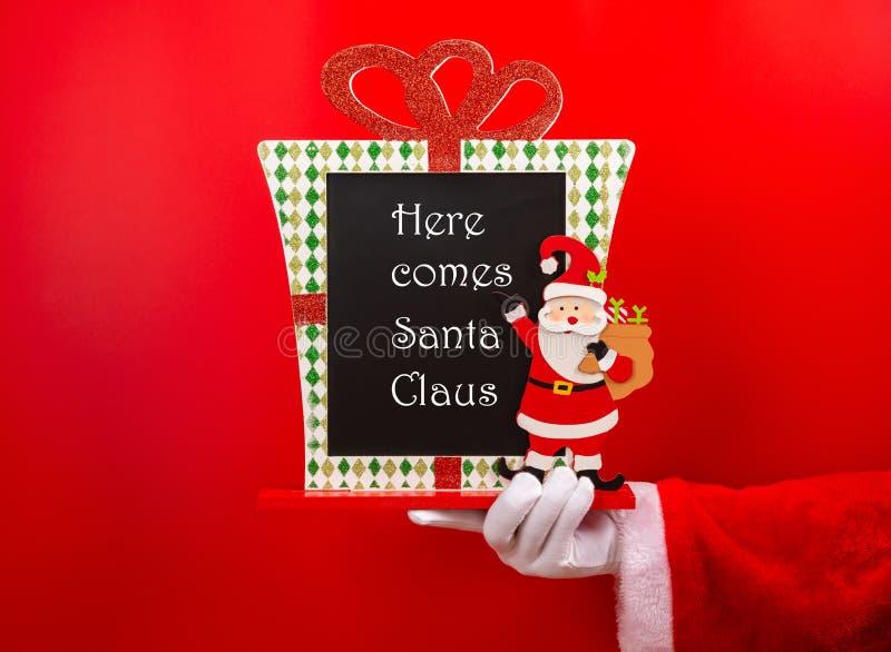 Santa Claus, die ein Weihnachten verziertes Kreidebrett mit hier hält, kommt Santa Claus auf Rot stockfotografie