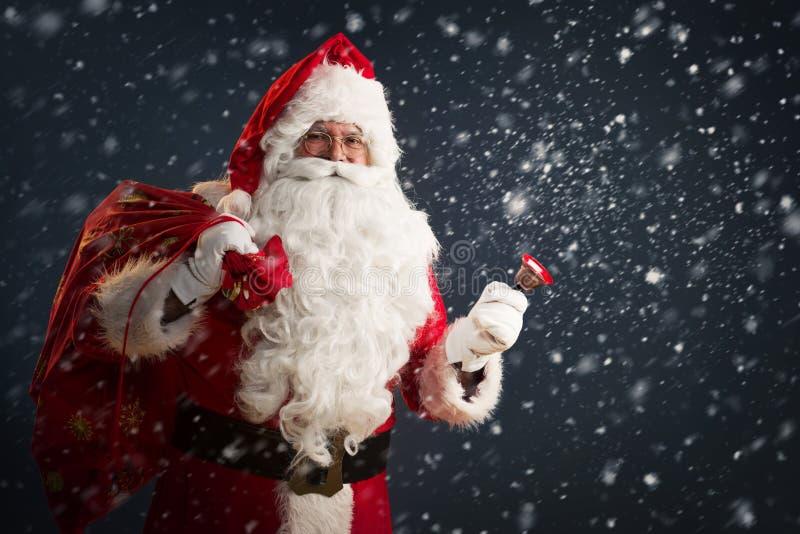 Santa Claus, die eine Tasche mit Geschenken hält und eine Glocke auf einem dunklen Hintergrund schellt stockbild