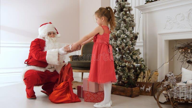 Santa Claus, die einem recht kleinen Mädchen Geschenke gibt und sie umarmt stockbild