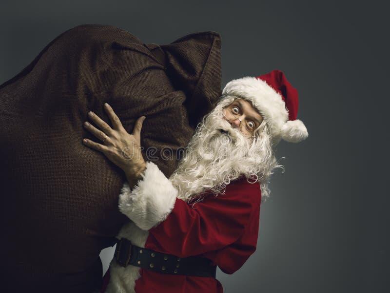 Santa Claus, die einen Sack mit Weihnachtsgeschenken trägt stockbild