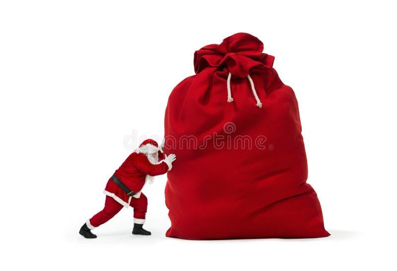 Santa Claus, die enormen Geschenkesack drückt lizenzfreies stockbild