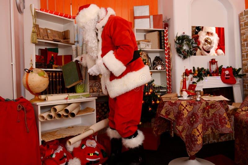 Santa Claus, die für Reise sich vorbereitet und nach Buch sucht stockbilder