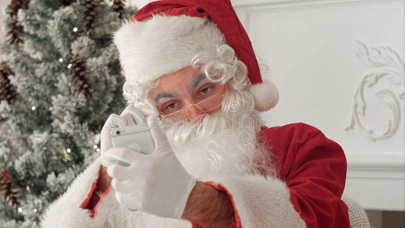 Santa Claus, die fröhliche selfies an seinem Telefon nimmt lizenzfreie stockbilder