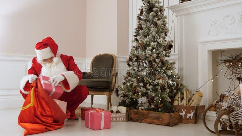 Santa Claus, die Geschenke zurück in seine Tasche durch Weihnachtsbaum setzt stockbild
