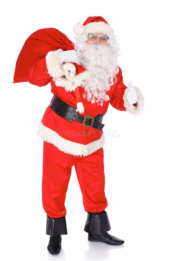 Santa Claus die grote zak dragen en duimen tonen of o.k. geïsoleerd op witte achtergrond Volledig lengteportret stock afbeeldingen