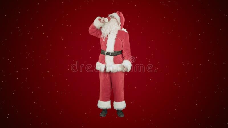 Santa Claus, die heißen Tee oder Kaffee und Wünsche frohe Weihnachten auf rotem Hintergrund mit Schnee trinkt stockfotografie