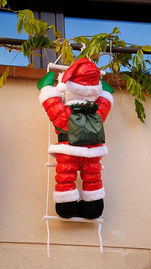 Santa Claus, die heraus das Fenster klettert lizenzfreies stockbild