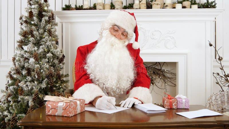 Santa Claus die Kerstmisbrieven in zijn workshop beantwoorden stock afbeeldingen