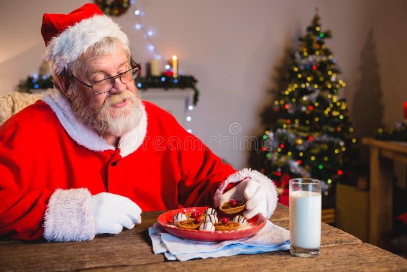 Santa Claus die koekje met een glas melk hebben stock foto