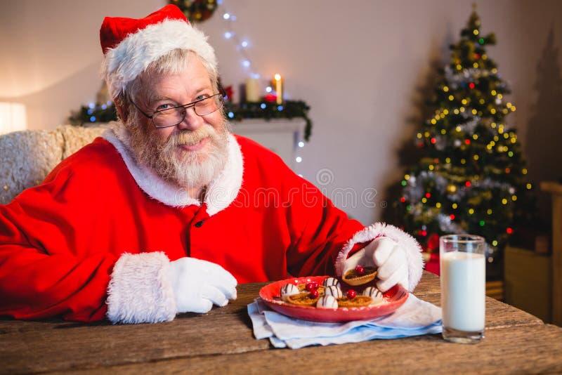 Santa Claus die koekje met een glas melk hebben royalty-vrije stock fotografie