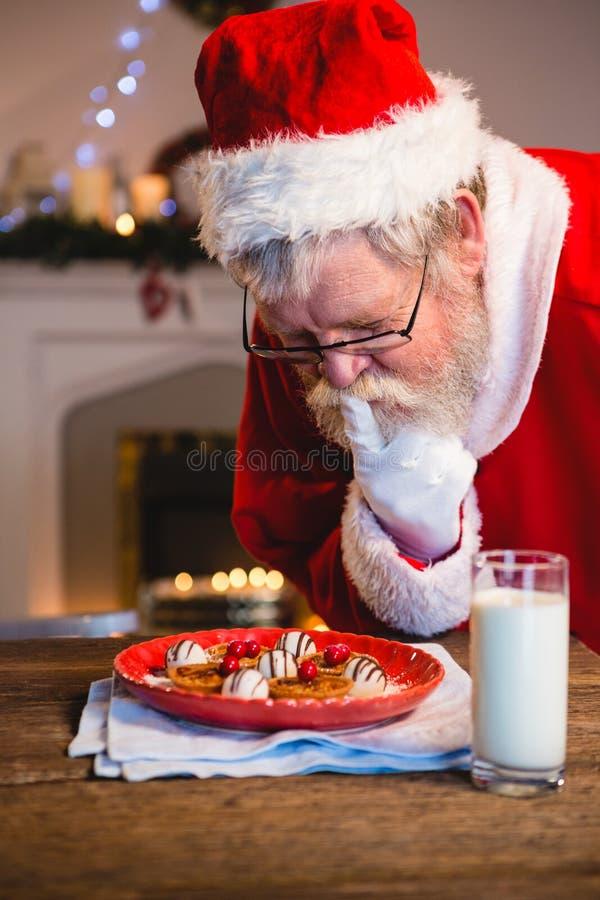 Santa Claus die koekjes van plaat selecteren stock foto