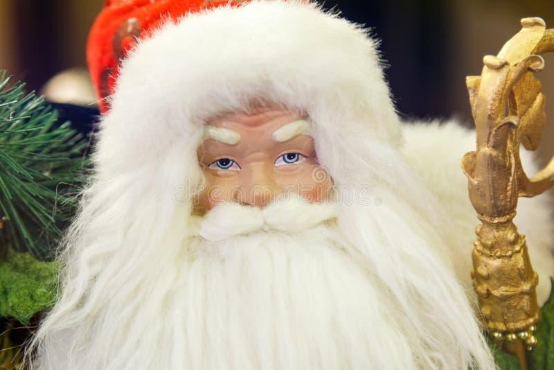 Santa Claus die met giften naast een Kerstboom zitten stock foto's