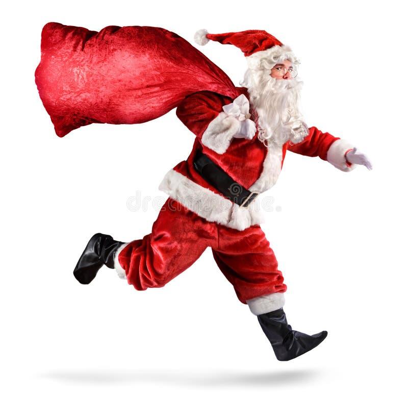 Santa Claus, die mit einer Tasche von Geschenken läuft stockfotografie