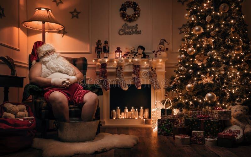 Santa Claus, die nach oder vor Arbeit sich entspannt lizenzfreie stockbilder
