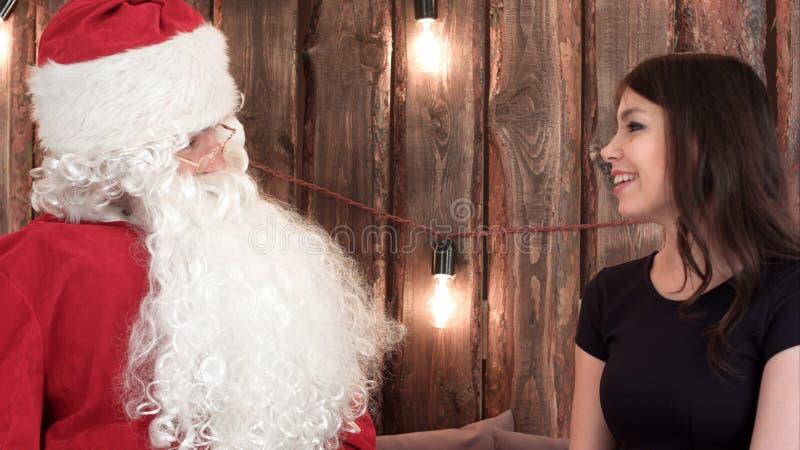Santa Claus, die nett mit einem recht jungen Brunette im schwarzen Kleid spricht stockfotos