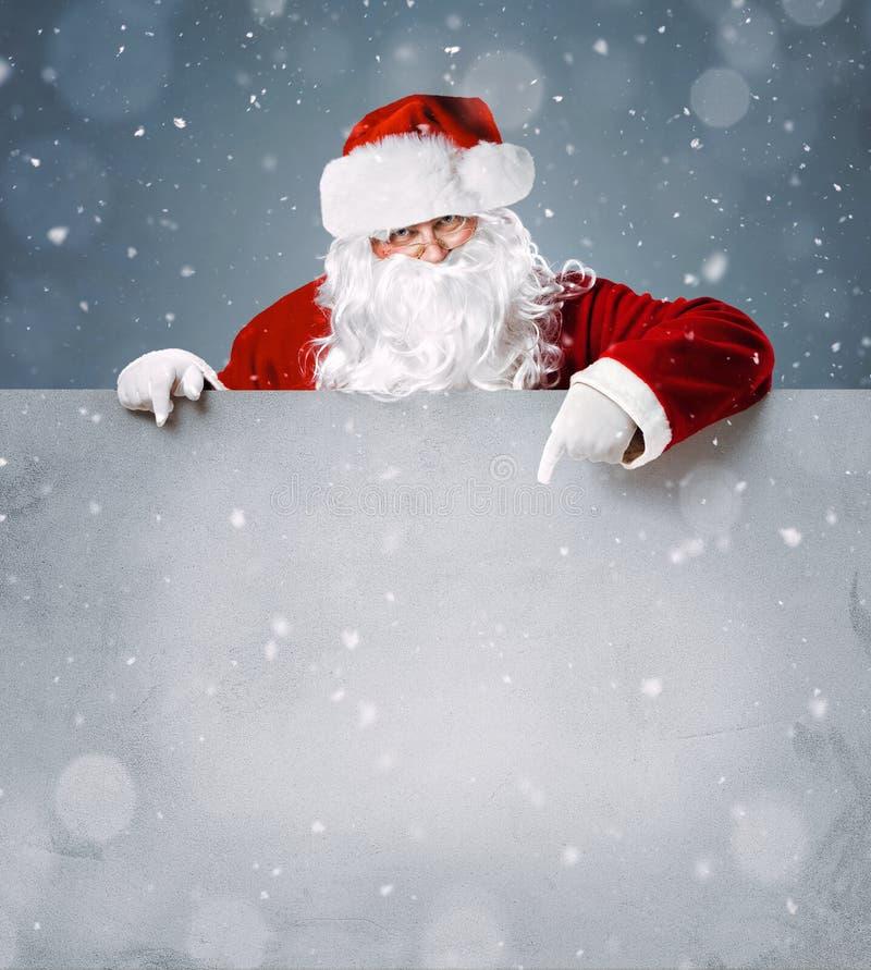 Santa Claus die op lege reclamebanner richten stock afbeeldingen