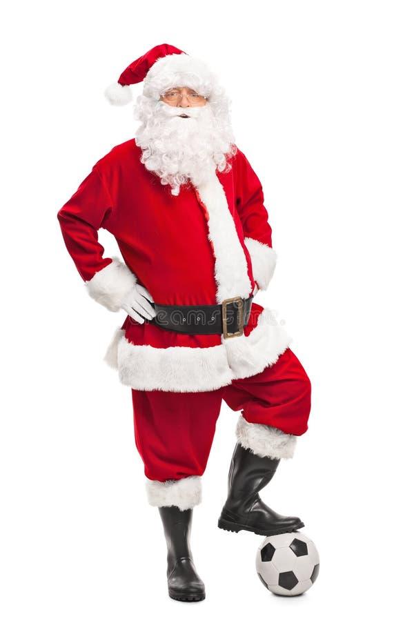 Santa Claus die over een voetbal stappen stock foto's