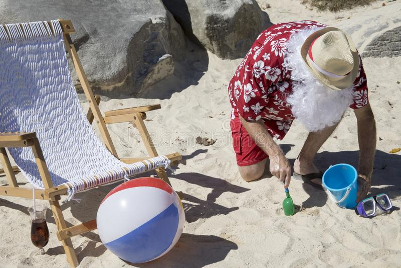 Santa Claus, die in Sand mit blassem und Schaufel gräbt lizenzfreie stockbilder