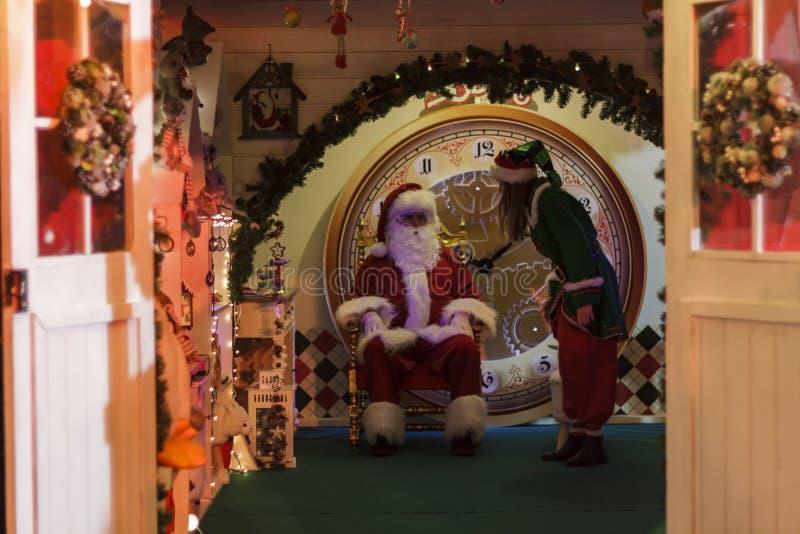 Santa Claus, die in seiner Lehnsessel- und Helferelfe sitzt lizenzfreies stockbild