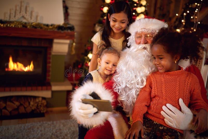 Santa Claus, die selfie während der Weihnachtsatmosphäre mit Kind nimmt stockbilder