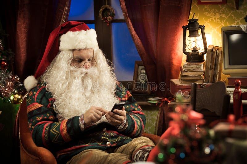 Santa Claus die smartphone gebruiken stock afbeelding