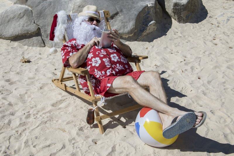 Santa Claus, die Tablette oder Eleser auf Strand verwendet lizenzfreie stockbilder