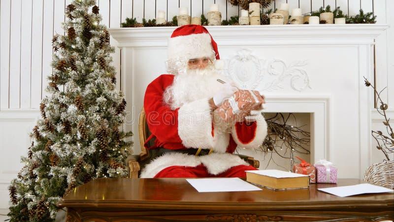 Santa Claus, die am Tisch in seinen unterzeichnenden Geschenken der Weihnachtswerkstatt für Kinder sitzt stockfoto
